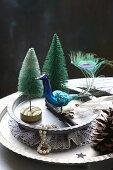 Winter arrangement of peacock figurine and miniature trees on metal plates
