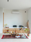 Fitted bench made from pale wood, coffee table, tea set on stool and houseplants in living room