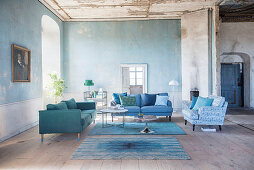 Sofas in shades of blue in living room of period building with distressed walls and ceilings