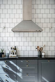Extractor hood above classic kitchen unit with grey cupboards