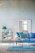 Living room in shades of blue and green with distressed wall