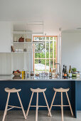 Three-legged barstools at blue kitchen counter in open-plan kitchen