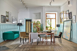 Various chairs around table in dining room with panelled wainscoting