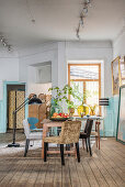 Various chairs around table in dining room with wainscoting