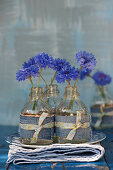 Cornflowers in small bottles with decoration