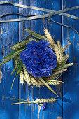 Arrangement of cornflowers in a wreath of wheat ears