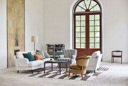 Various upholstered furnishings on striped rug in front of arched window