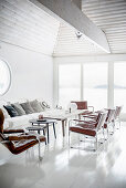 Leather armchairs in white, light-flooded living room