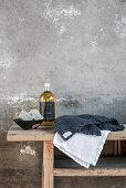 Handtücher, Flasche und Schale mit Seifen auf Holzbank