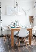 Holztisch und weiße Schalenstühle im sommerlichen Esszimmer