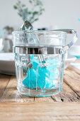 Blaue Eiswürfel im transparenten Behälter mit Zange