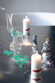 Candles, porcelain and glass figures on festively painted table
