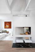 Upholstered stools in front of modern open fireplace in white living room