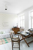 Chairs around old folding table in living room with polka-dot wallpaper