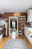 Rustic wooden walls in Bohemian-style country-house kitchen
