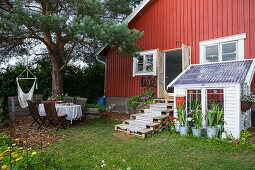 Falu-red wooden house with lean-to greenhouse and summery garden