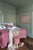 Panelled walls and pink accents in classic bedroom