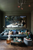 Petrol-blue velvet sofa below retro photographic art print in glamorous living room