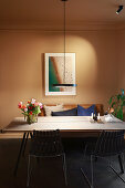 Modern pendant lamp above dining table against beige wall