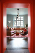 View through red door frame into living room in muted shades