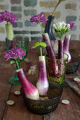 Chrysanthemums and bouvardia in hollowed-out spring onions used as vases