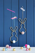 Easter bunnies made from knitted tubes, wire and pompoms on wall