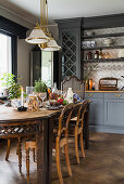 Rustic wooden table in country-house-style dining room with wooden floor