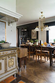 Antique, solid fuel cooker in open-plan kitchen and rustic wooden table in dining area