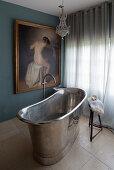 Freestanding, metal bathtub and classic painting in bathroom