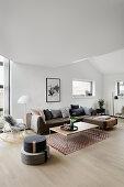 Grey corner sofa and floor cushions in modern, open-plan interior