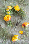 Tie a wreath of rose blossoms and grass