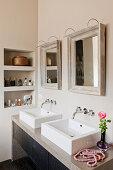 Zwei Spiegel über eckigen Doppelwaschbecken im Bad in Beige