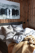 Rumpled bed in cosy bedroom with wood-clad walls
