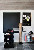Eames' Leg Splint sculpture, black pinboard and trolley in study