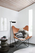 Classic leather Butterfly Chair, standard lamp and side table in corner