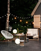 Seats and strings of fairy lights on night-time terrace