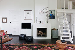 Leather chair and pouffes in front of fireplace in living room with ships' ladder stairs leading to gallery