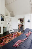 Sofa and Oriental rug in living room with ships' ladder stairs leading to gallery