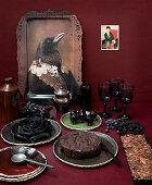 Bird portrait on tray and buffet of cakes on red table against red wall