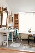 Vintage Standwaschbecken unter gerahmtem Spiegel und Badewanne vor Fenster