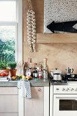Küchenzeile mit Betonplatte neben Gasherd, Knoblauchzopf an der Wand