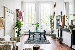 Glastisch mit Stühlen vor Sprossenfenster, Kaminattrappe und Zimmerpflanzen in Altbauwohnung