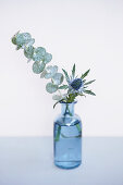 Eucalyptus and sea holly in glass bottle