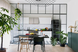 Dining table with various chairs in front of kitchen with glass-and-steel wall