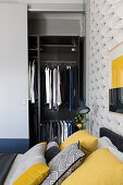 Open wardrobe in grey bedroom with yellow accents