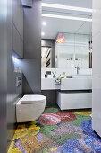 Mosaic floor tiles with pixelated floral motif in modern bathroom