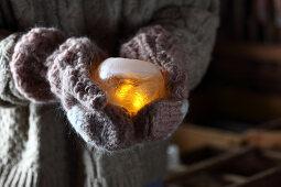 Hände in Handschuhen halten Windlicht aus Eis