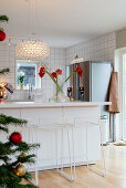 Slender barstools at counter in open-plan kitchen decorated for Christmas