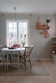 Round table and chairs with turned legs and spokes in rustic kitchen-dining room