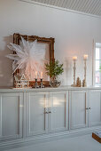 Paper star hung on gilt picture frame and gingerbread house on sideboard